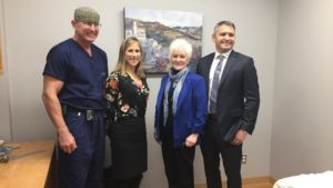 Orthopedic surgeon Dr. Dave Puskas (far left), Rapid Access Clinic program director Caroline Fanti (left), patient Laurie Horlick (centre) and orthopedic surgeon Dr. Travis Marion (right) stand in a treatment room at the innovative new clinic at the Thunder Bay Regional Health Sciences Centre. (Cathy Alex/CBC )